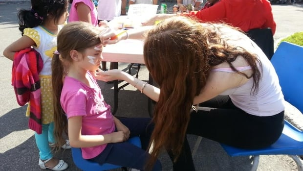 Kids take a break from soccer, games and BBQ to get their faces painted during the Tyndale St-Georges Community BBQ last June.