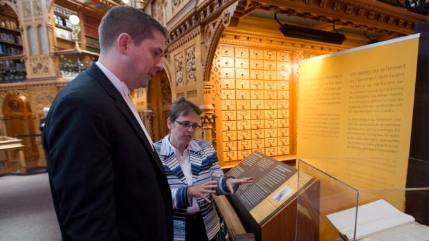 Parliamentary Librarian Sonia L'Heureux talks to Speaker of the House of Commons Andrew Scheer about a scrapbook of early newspaper clippings about Canadian parliament during an event in the library on Parliament Hill Tuesday May 27, 2014 in Ottawa.
