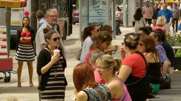 Winnipeggers enjoy the heat during a noon hour break along Broadway on Thursday.