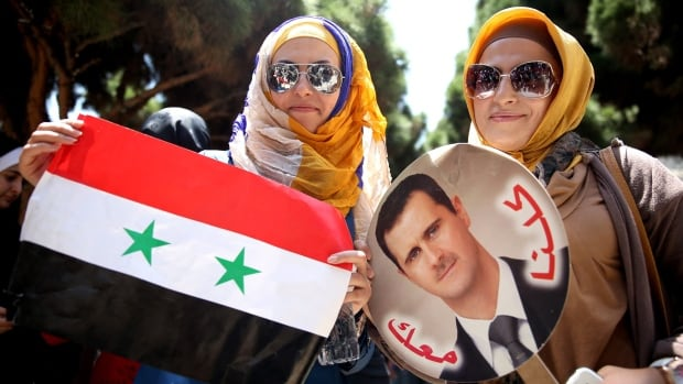 Two Syrian women who live in Iran hold their country's flag and a picture of Syrian President Bashar al-Assad after casting their votes for their country's presidential election. Thousands of people have fled government-held Syrian cities after opposition fighters warned they will attack during next week's presidential election.