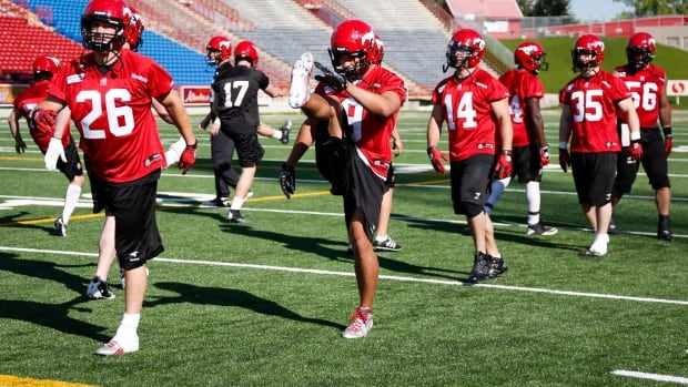 Calgary Stampeders' Rob Cote, left, and Jon Cornish, centre, take part in a drill during the first day of training camp on Sunday.