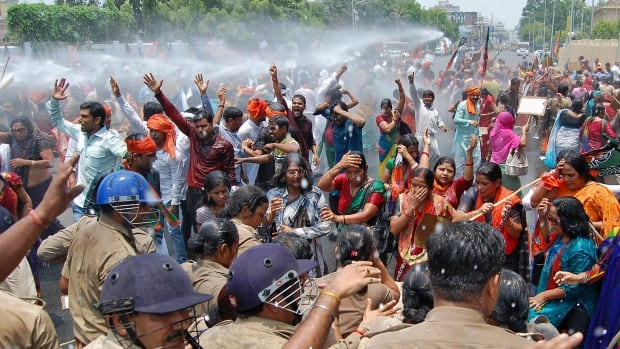 Supporters of the Bharatiya Janata Party brace against police water cannon in Lucknow.