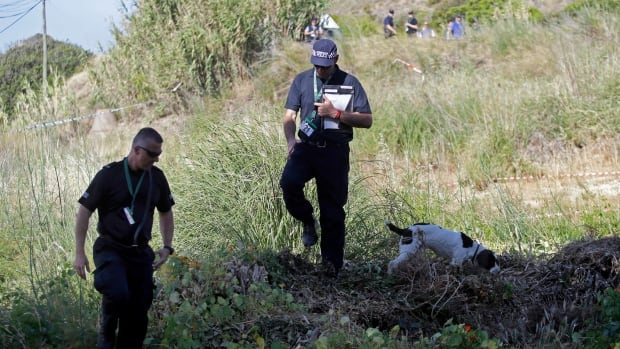 British policemen and a police search dog probe a cordoned-off area, in Praia da Luz, Lagos, southern Portugal on Tuesday.