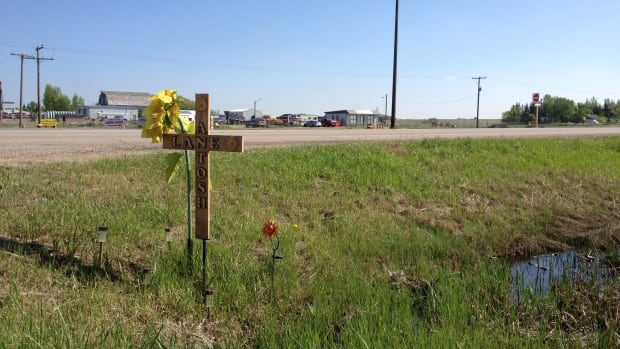 A cross marks the spot of a traffic fatality on Highway 1 east of Regina, near Pilot Butte. The province has lowered speed limits on the section.