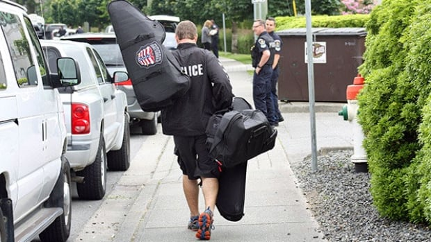An emergency response team member arrives at the scene of a police standoff on Bourquin Crescent in Abbotsford on Tuesday afternoon with gear in hand.