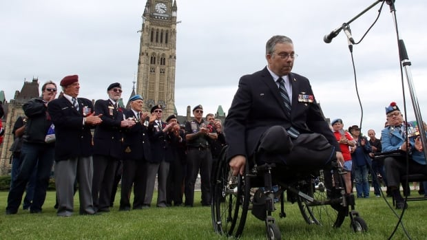Retired major Mark Campbell talks to reporters during a war veterans rally on Parliament Hill in Ottawa, Wednesday. He says that after many disappointments, he doesn't trust politicians as far as he can throw them.