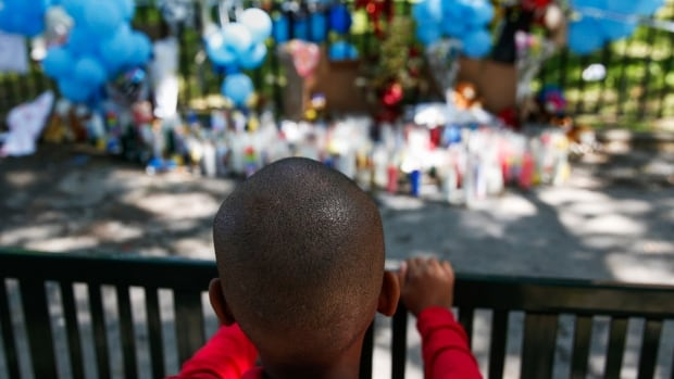 Donta'e Acker, 8, looks at a makeshift memorial in the Brooklyn borough of New York after two young children were stabbed, one fatally, in an elevator in a New York City apartment building.