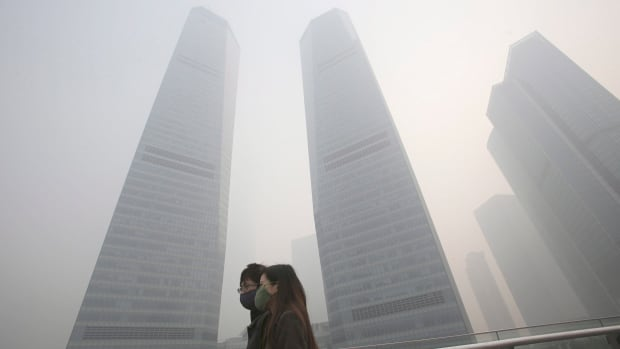 A couple in protective masks walk under haze in Shanghai, China, on Dec. 6, 2013. The IMF is warning China about its rising debt levels.