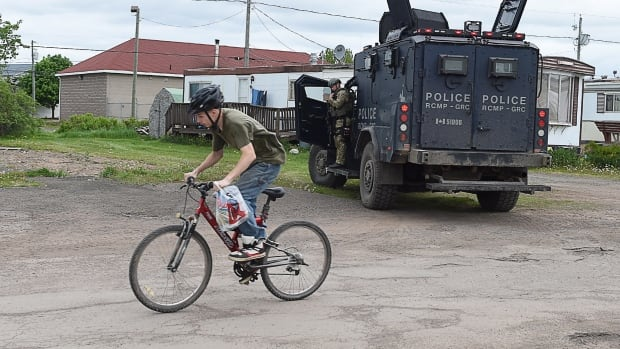 A youth rides his bike past a trailer where murder suspect Justin Bourque, 24, resides in Moncton, N.B., on Thursday, June 5, 2014. Bourque is wanted after three RCMP officers were killed and two injured by a gunman wearing military camouflage and wielding two guns on Wednesday.