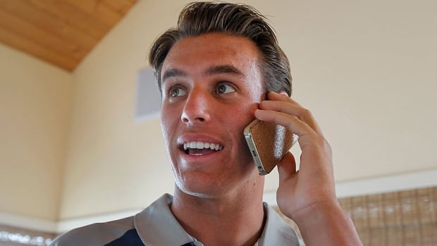California high school pitcher Brady Aiken glances up at the MLB draft being televised as he receives a congratulatory phone call just after he was selected first overall by the Houston Astros on Thursday night.