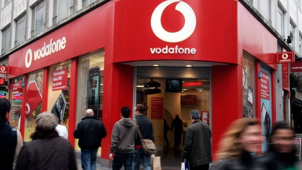 People walk by a Vodafone branch in central London. Vodafone revealed the scope of government snooping into phone networks in a report released Friday.