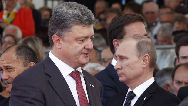 Ukraine's President-elect Petro Poroshenko, left, walks past Russian President Vladimir Putin during the commemoration of the 70th anniversary of the D-Day in Ouistreham, western France. Ukraine will be watching to see how the new president handles a seething eastern rebellion.