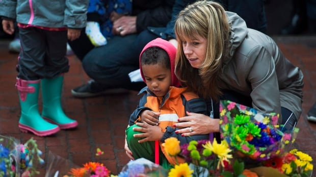 A woman and child participate in a candle light vigil in Moncton, N.B. on Friday, June 6, 2014 to pay respect to the three RCMP officers who were killed and the two injured in a shooting spree on Wednesday. Justin Bourque, 24, is facing three charges of first-degree murder and two charges of attempted murder.