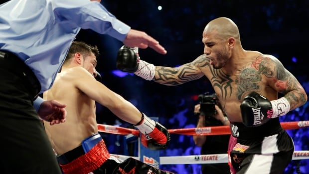 Miguel Cotto of Puerto Rico knocks down Sergio Martinez, of Argentina, during the first round of a WBC middleweight title boxing match at Madison Square Garden on Saturday in New York.