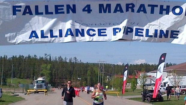 Participants cross the finish line in Whitecourt for the Fallen 4 Marathon.