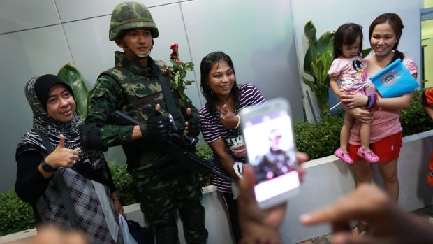 "A Thai soldier poses for photograph with Thai-Muslim women during an event called ""Return Happiness to Thai People"" in Bangkok."