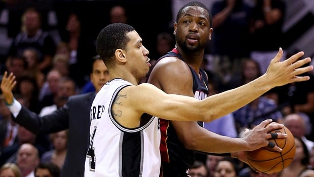 Dwyane Wade, right, of the Heat is covered closely by Danny Green in a 98-96 victory over the Spurs in Game 2 on Sunday.
