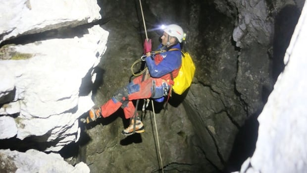 A picture provided by Bavarian Red Cross/Berchtesgaden shows a rescuer entering a cave near Berchtesgaden, Germany, to recover a man stuck deep inside the Riesending cave system.