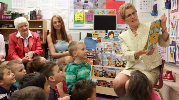 Ontario Liberal Leader Kathleen Wynne reads a story to kindergarten students during a campaign stop at a school in Cambridge, Ont., on Monday. She said the province's education system is under threat from the Tories' pledge to cut 100,000 jobs, including thousands in education.