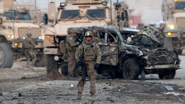 U.S. troops stand guard at the site of an attack in Kabul earlier this year. 5 American NATO service members were killed in southern Afghanistan on Monday, officials said Tuesday.