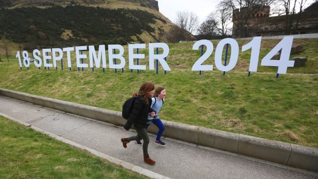 A teacher and schoolgirl run in front of a sign indicating the date of Scotland's independence referendum outside the Scottish Parliament in Edinburgh. Scotland will hold its independence referendum on Sept. 18.