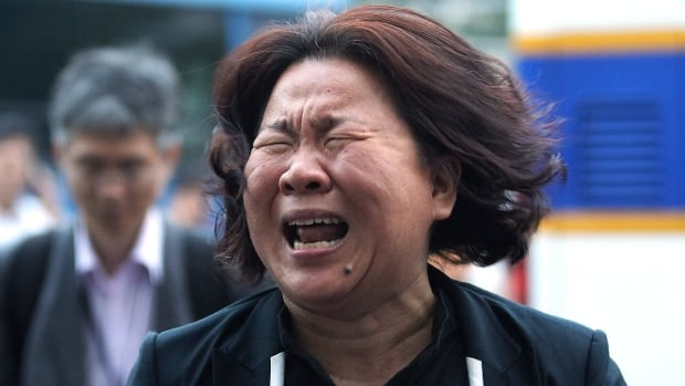 A family member of passengers aboard the sunken ferry Sewol cries after attending a court appearance of the crew members of the ferry at Gwangju District Court in Gwangju, South Korea, on Tuesday. eleven of the 15 crew members who appeared in court entered pleas of not guilty on charges of negligence and failing to save more than 300 dead or missing passengers. The other four will enter their pleas next week.