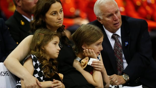The family of RCMP officer Douglas James Larche, one of three officers who were killed last week, reacts during a regimental funeral in Moncton on Tuesday.