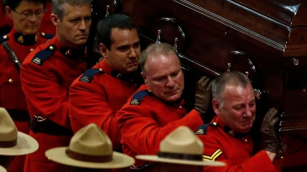 Pallbearers carry the casket of one of three RCMP officers killed in 2014 by a gunman. The Mounties launched a series of lab tests on popular semi-automatic rifles after learning the gunman had considered converting his weapon to fire like an automatic. The tests showed the illegal upgrades worked.