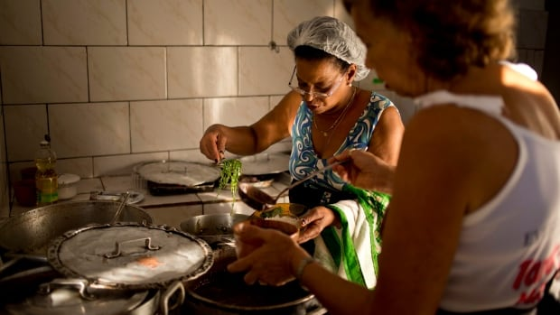 In this 2012 photo, Marineteh Pinto, left, cooks a traditional bean and meat stew called feijoada in Rio de Janeiro, Brazil.