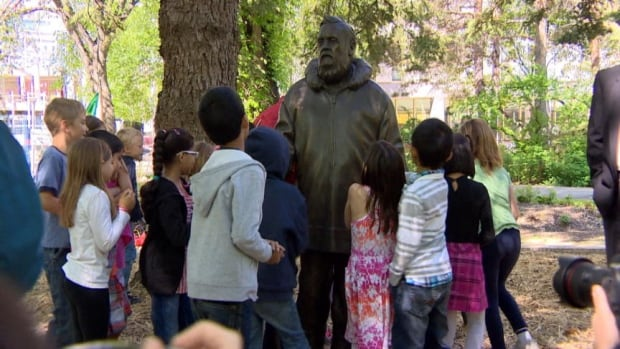 Youngsters from a Grade 2 class at Lakeview School in Saskatoon check out a new statue of author Farley Mowat, unveiled on the grounds of the University of Saskatchewan.