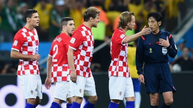 Referee Yuichi Nishimura, right, is pursued by Croatian players during the match against Brazil.