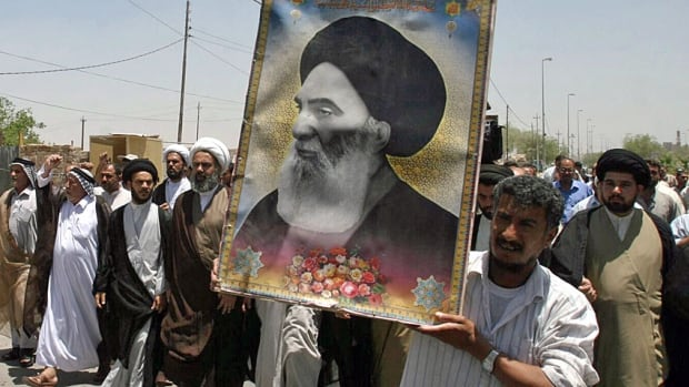 A 2007 file photo shows Iraqis carrying a poster of top Shia cleric Grand Ayatollah Ali al-Sistani, who issued a call to arms on Friday for Shia in Iraq to fight against Sunni militants who have seized large swaths of territory in the north.