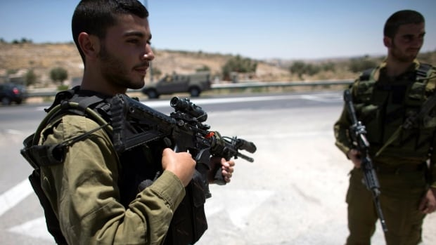 Israeli soldiers stand guard near the West Bank city of Hebron on Saturday.  Israel was reinforcing troops in the occupied West Bank on Saturday to step up searches for three Israeli teenagers believed to have been abducted by Palestinians, a military source said.