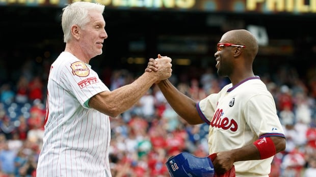 The Phillies' Jimmy Rollins, right, celebrates his single with former Philadelphia third baseman Mike Schmidt during the fifth inning of Saturday's game against the Chicago Cubs in Philadelphia. The single gives Rollins the all time hits mark for the Phillies over Schmidt with 2,235.