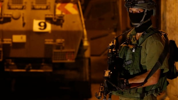 An Israeli soldier stands guard in the West Bank city of Hebron on Sunday. Israel sent more troops to the occupied West Bank on Saturday to step up searches for three Israeli teenagers believed to have been abducted by Palestinians.