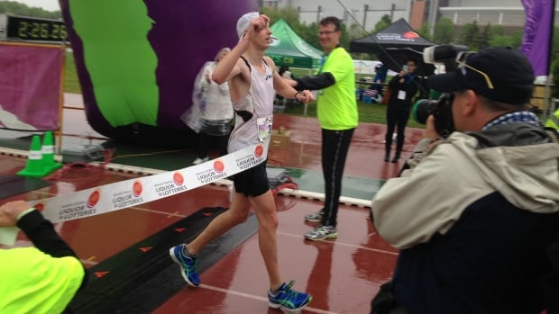 Brian Walker crosses the finish line as the men's full marathon winner at the Manitoba Marathon on Sunday morning.