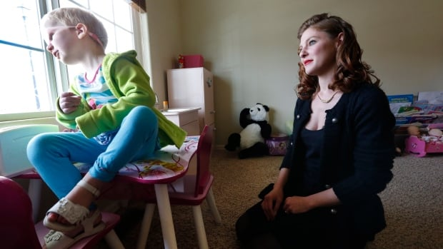 Moriah Barnhart watches her three-year-old daughter Dahlia, who has cancer, at their home in Colorado Springs. Barnhart is facing the possibility of intervention by child protective authorities because she's treating her child with cannabis medication.