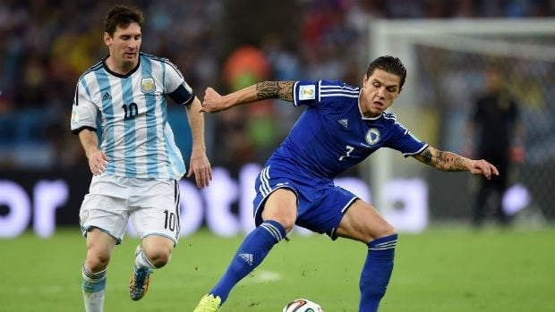 Muhamed Besic of Bosnia-Herzegovina, right, controls the ball against Lionel Messi of Argentina.