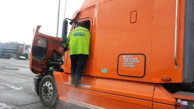 Police inspect a tractor-trailer that was seen spewing white smoke on Monday morning.