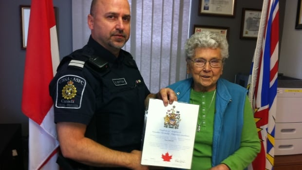 CBSA Supt. Brad Britton presents 'new' Canadian Olga Ogloff with her citizenship.