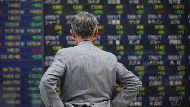 A man looks at an electronic stock board of a securities firm in Tokyo. A new study finds that insider trading is more pervasive than has been suspected.