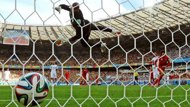 Marouane Fellaini of Belgium, right, scores his team's first goal on a header past Rais M'Bolhi of Algeria.