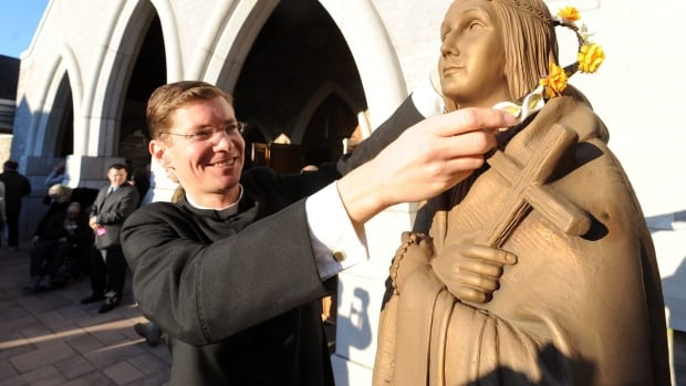 A clergy member places flowers on a statue of Saint Kateri Tekakwitha at Saint Kateri Tekakwitha Roman Catholic Church in Lagrangeville, N.Y., in 2012. Because of Canada's residential school history, many people assume today's Aboriginal Peoples want little to do with the church.