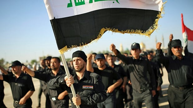 Mehdi Army fighters loyal to Shia cleric Moqtada al-Sadr march during a military-style training in the holy city of Najaf on Tuesday. The reaction to the surprising advances of the al-Qaeda related group, ISIS, was quickly breaking down along sectarian lines.