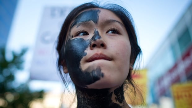 Jacqueline Lee-Tam wears face paint to simulate oil while attending a rally held to show opposition to the Enbridge Northern Gateway pipeline in Vancouver on Tuesday. The federal government is giving a conditional green light to Enbridge Inc.'s controversial $7-billion Northern Gateway pipeline project between the Alberta oilsands and the B.C. coast.