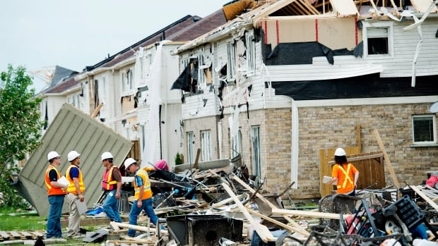 Investigators assess the damage to homes and property, a day after a tornado touched down in Angus, Ont.