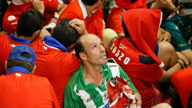 Chile fans sit on the ground after they broke into the press centre prior to the match between Spain and Chile at the Maracana Stadium in Rio de Janeiro, Brazil on Wednesday.  (Frank Augstein/Associated Press)