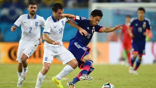 Giorgos Karagounis of Greece, left, challenges Shinji Kagawa of Japan.