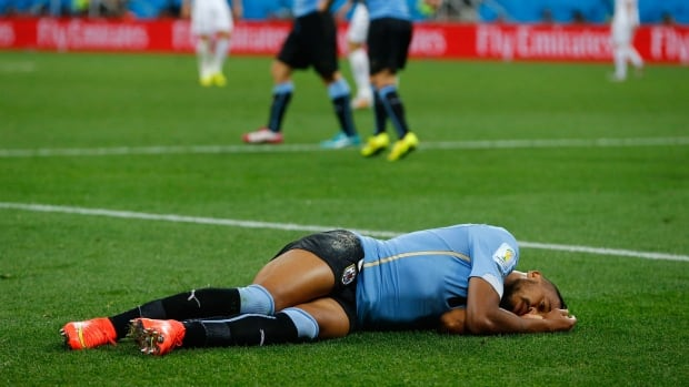 Uruguay's Alvaro Pereira is knocked out after taking a knee to the head during Thursday's FIFA World Cup match against England. The players' union says he shouldn't have been allowed to return to the match.
