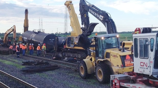CN crews work to get a crude oil tanker car back on the tracks at Symington Yards.